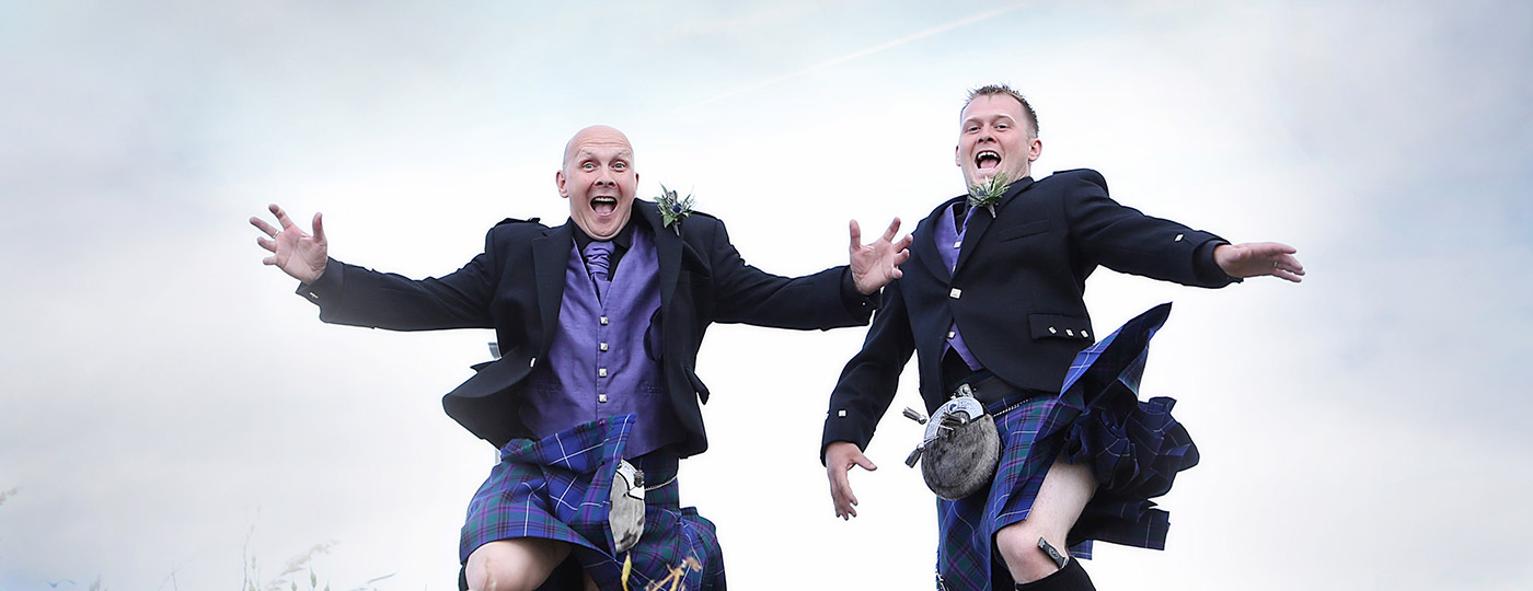 two Men jumping in Kilts